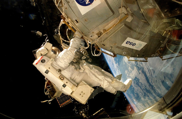 An astronaut fixes the EXPOSE-E platform onto the International Space Station.