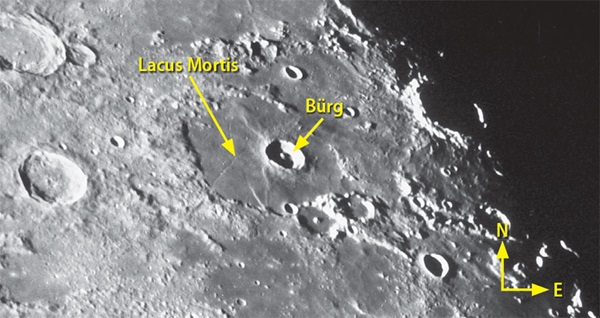 The sharp rim of the 25-mile-wide crater Bürg stands out against the smooth lava plains of Lacus Mortis.