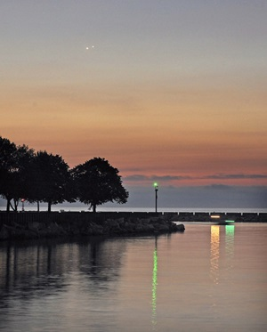 Venus (left) and Jupiter glow in the early dawn as they rise above Milwaukee's McKinley Marina on Monday morning, August 18.