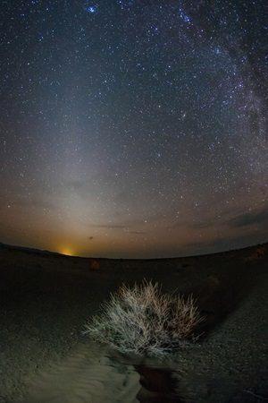 The zodiacal light comes from tiny particles in the plane of our solar system scattering sunlight.