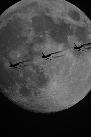 A jet crosses the face of the Moon
